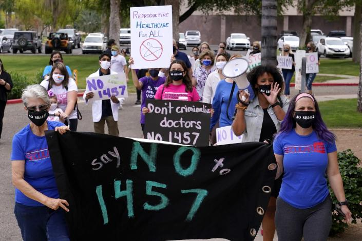 A number of Arizona reproductive rights groups march to deliver a petition to Gov. Doug Ducey to veto SB 1457, the latest abortion bill passed by the state legislature last week, at the Arizona Capitol Monday, April 26, 2021, in Phoenix. (AP Photo/Ross D. Franklin)