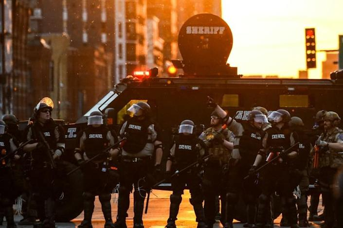 Minnesota State Police officers in front of an armored sheriff's vehicle on May 31, 2020 in Minneapolis, during a protest against police brutality after the killing of George Floyd days earlier (AFP Photo/CHANDAN KHANNA)