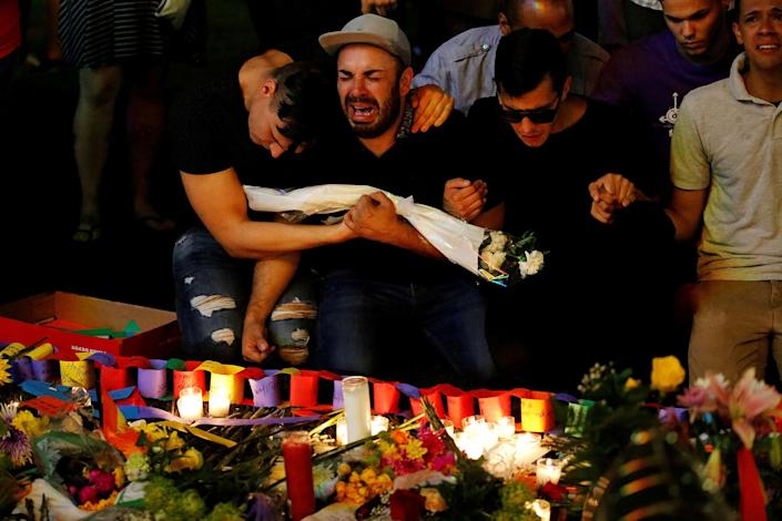 <p>JUN. 13, 2016 — A man sits and cries after taking part in a candlelight memorial service the day after a mass shooting at the Pulse gay nightclub in Orlando, Florida. (Carlo Allegri/Reuters) </p>