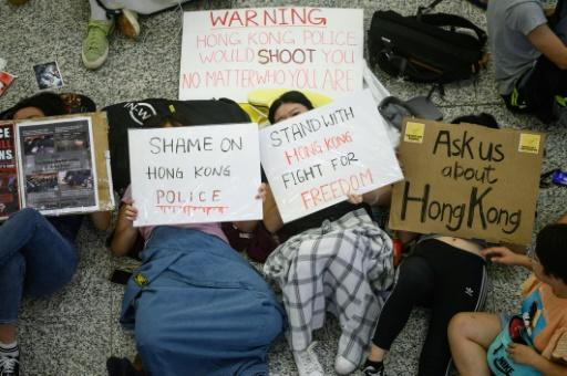 Protesters hold placards as they rest on the floor of Hong Kong's international airport