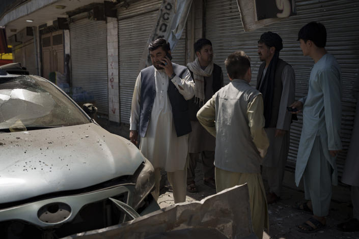 Afghans gather at the site of an explosion in Kabul, Afghanistan, Saturday, Sept. 18, 2021. A sticky bomb exploded in the capital Kabul wounding a few people, said police officials. (AP Photo/Felipe Dana)