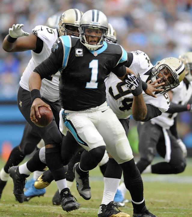 Carolina Panthers' Cam Newton (1) runs away from New Orleans Saints' Cameron Jordan (94), and Tyrunn Walker (75) in the first half of an NFL football game in Charlotte, N.C., Sunday, Dec. 22, 2013. (AP Photo/Mike McCarn)