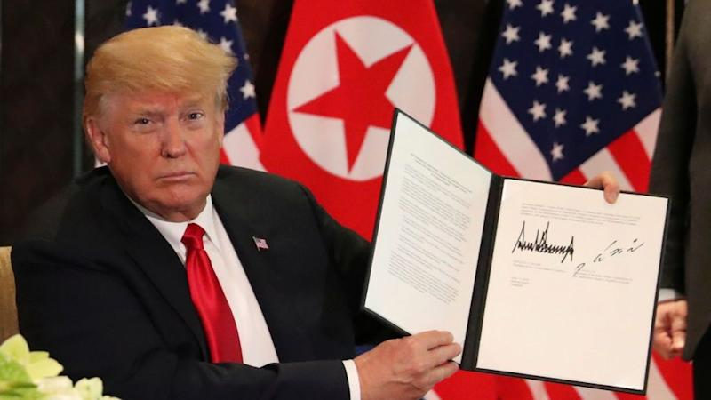 U.S. President Donald Trump shows the document, that he and North Korea's leader Kim Jong Un signed acknowledging the progress of the talks and pledge to keep momentum going, after their summit at the Capella Hotel on Sentosa island in Singapore June 12, 2018.