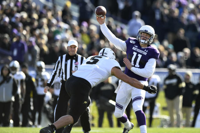 Northwestern quarterback Aidan Smith (11) gets off a touchdown pass to wide receiver Jace James while Purdue defensive end George Karlaftis (5) defends during the first half of an NCAA college football game, Saturday, Nov. 9, 2019, in Evanston, Ill. (AP Photo/Paul Beaty)