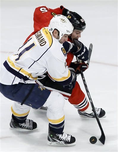 Nashville Predators center David Legwand (11) keeps Chicago Blackhawks center Andrew Shaw from taking a shot during the second period of an NHL hockey game Tuesday, Jan. 24, 2012, in Chicago. (AP Photo/Charles Rex Arbogast)