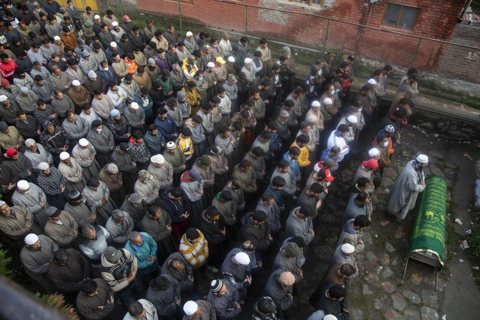Kashmiri villagers offer funeral prayer near the coffin of elected official Riyaz Ahmad in Sopore 55 kilometers (34 miles) north of Srinagar, Indian controlled Kashmir, Monday, March. 29, 2021. Gunmen killed an elected official of India's ruling party and a policeman in disputed Kashmir on Monday, police said. Police blamed anti-India militants for the attack. None of the rebel groups that have been fighting against Indian rule since 1989 immediately claimed responsibility for the attack. (AP Photo/Mukhtar Khan).