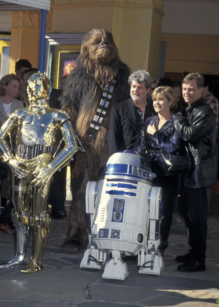 C-3PO, Chewbacca, R2-D2, George Lucas, Carrie Fisher and Mark Hamill.