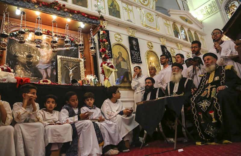 Egyptian Christian boys and priests pray during the Good Friday procession at the St. George church in the city of Mahalla in the north of Egypt, on April 14, 2017 (AFP Photo/STRINGER)