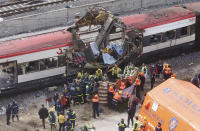 FILE - In this March 11, 2004 file photo rescue workers cover up bodies alongside a bomb-damaged passenger train, following a number of explosions in Madrid, Spain, March 11, 2004. In the 20 years since the Sept. 11, 2001 terrorist attacks in the United States, a mixture of homegrown extremists, geography and weaknesses in counterterrorism strategies have combined to turn Europe into a prime target for jihadists bent on hurting the West. (AP Photo/Paul White, File)