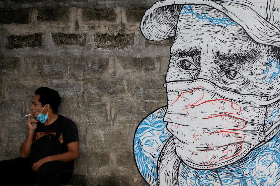 A man smokes a cigarette next to a mural of a man wearing a protective mask amid the coronavirus disease (COVID-19) outbreak in Quezon City, Metro Manila, Philippines, July 30, 2020. REUTERS/Eloisa Lopez