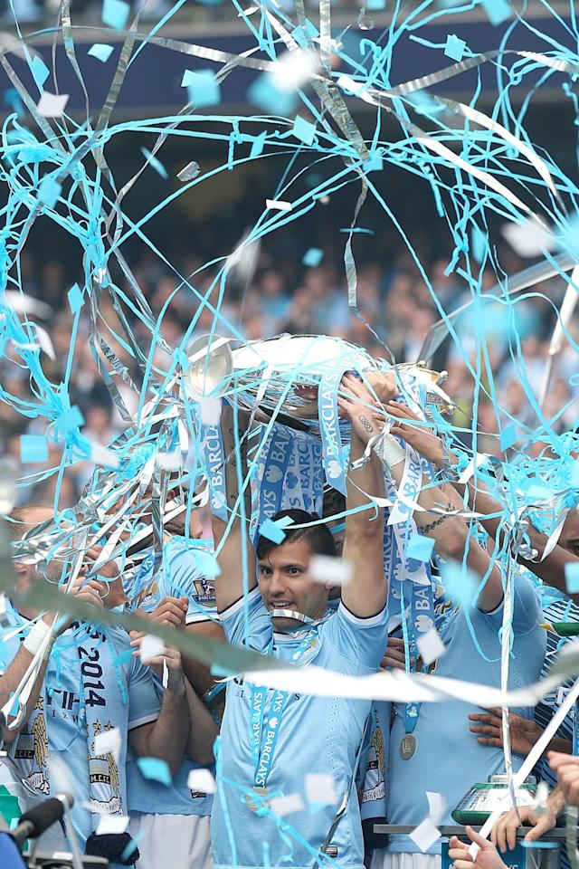 Manchester City's Sergio Aguero celebrates with the Premier League Trophy after his team's 2-0 win against West Ham in their English Premier League soccer match at the Etihad Stadium in Manchester, England, Sunday May 11, 2014. (AP Photo/Lynne Cameron, PA Wire)