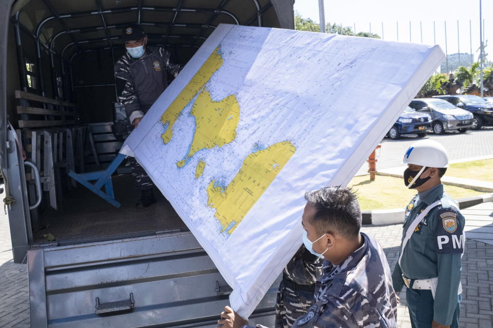 Military personnel load a map of the search area for the missing submarine onto a truck at Ngurah Rai Airport in Bali.