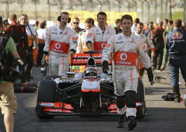 McLaren Formula One driver Jenson Button of Britain is guided by his mechanics towards his starting grid ahead of the Formula One Japanese Grand Prix in Suzuka October 13, 2013. REUTERS/Toshifumi Kitamura/Pool (JAPAN - Tags: SPORT MOTORSPORT F1)