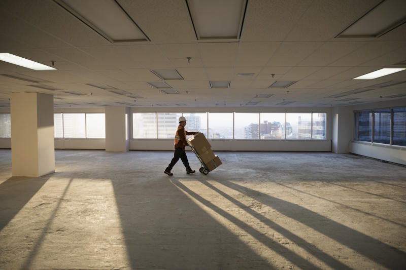 Construction worker moving cardboard boxes on handcart in sunny empty, unfinished highrise office