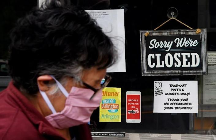 A woman wearing a face mask walks past a sign saying a food store is closed in Arlington, Virginia in May 2020 (AFP Photo/Olivier DOULIERY)