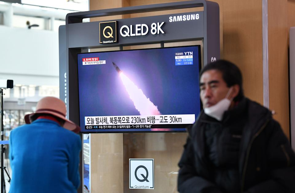 People watch a news broadcast showing file footage of a North Korean missile test, at a railway station in Seoul on March 29, 2020. - North Korea fired what appeared to be two short-range ballistic missiles off its east coast on March 29, the fourth such launch this month as the world battles the coronavirus pandemic. (Photo by Jung Yeon-je / AFP) (Photo by JUNG YEON-JE/AFP via Getty Images)