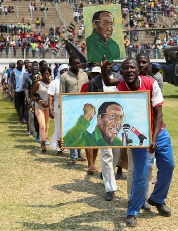 Mourners hold paintings with the face of former Zimbabwean president Robert Mugabe, as they queue to pay their last respects as he lies in state at the at Rufaro stadium, in Mbare