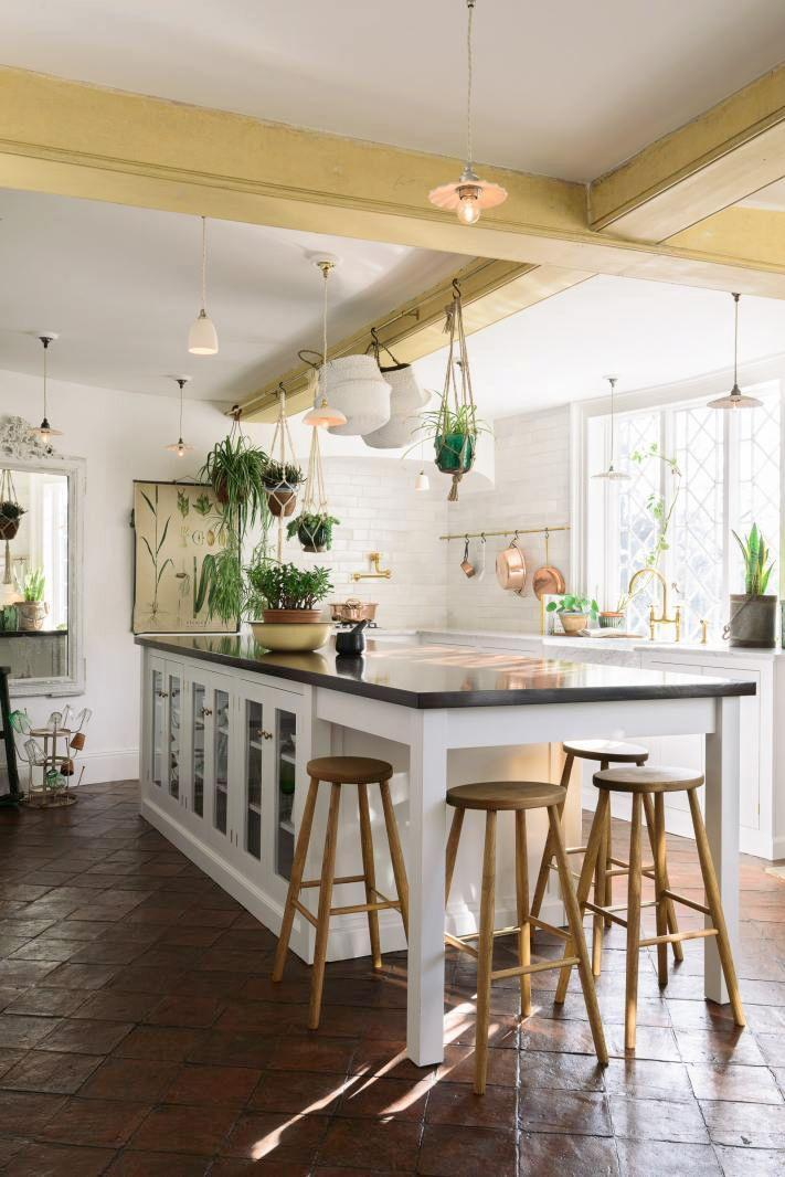 <p>This country chic kitchen by deVOL is so full of life. The light yellow-painted beams fill it with a sunny energy while the hanging plants and framed plant print make it feel fresh and easygoing, as do the laidback terra cotta floor tiles. </p>