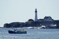 HOLD FOR RELEASE FRIDAY, SEPT. 25 - A lobster boat hauls traps near Portland Head Light, Monday, Sept. 21, 2020, off Cape Elizabeth, Maine. Prices for consumers and wholesalers were low in the early part of the summer, but picked up in August to the point where they were about on par with a typical summer. (AP Photo/Robert F. Bukaty)