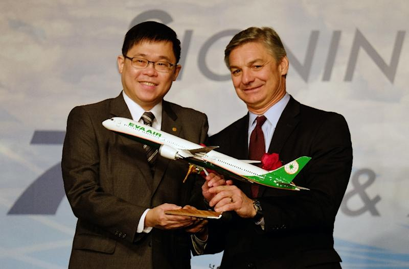 Chang Kuo-wei (L), chairman of Taiwan's Eva Air, receives a Boeing 787 model plane from Ray Conner, president and CEO, Boeing Commercial Airplanes, in Taipei on November 24, 2015