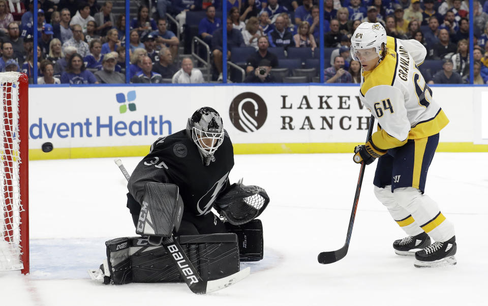Nashville Predators center Mikael Granlund (64) watches a shot by teammate Calle Jarnkrok, not shown, get by Tampa Bay Lightning goaltender Curtis McElhinney (35) for a goal during the first period of an NHL hockey game Saturday, Oct. 26, 2019, in Tampa, Fla. (AP Photo/Chris O'Meara)