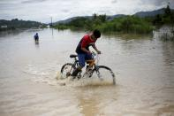 A child rides his bicycle on a flooded road during the passage of Storm Eta, in Pimienta