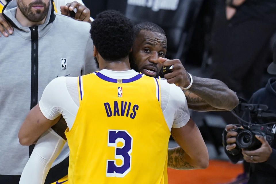 Los Angeles Lakers forward LeBron James, rear, hugs forward Anthony Davis (3) after Game 2 of the team's NBA basketball first-round playoff series against the Phoenix Suns on Tuesday, May 25, 2021, in Phoenix. The Lakers won 109-102. (AP Photo/Ross D. Franklin)