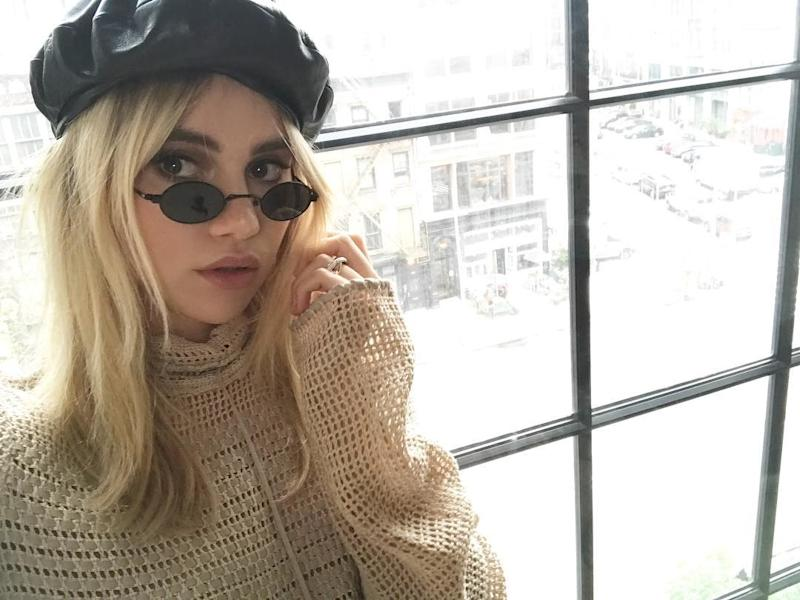 Suki Waterhouse poses for an Instagram selfie wearing Matrix sunglasses and a black leather beret.