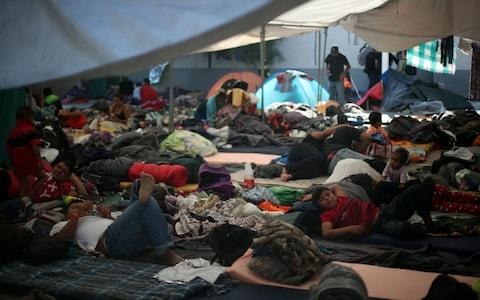 Migrants, part of a caravan of thousands from Central America trying to reach the United States, rest in a temporary shelter in Tijuana - Credit: HANNAH MCKAY/REUTERS