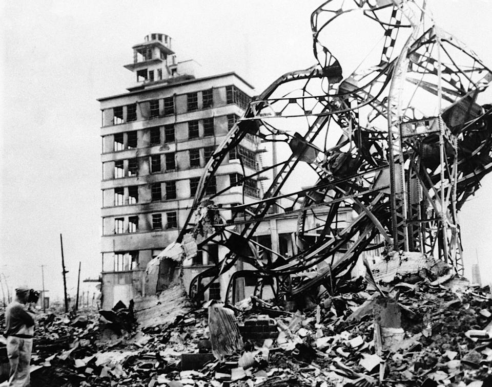A twisted mass of steel, marks the site of a large building in the industrial centre of atomized Hiroshima, Japan, on Sept. 13, 1945, directly behind, in grim contrast, a partly demolished building towers up, amid acres of gutted and fire blackened debris.