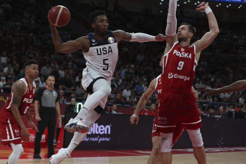United States' Donovan Mitchell attempts to pass the ball near Poland's Mateusz Ponitka at right during a consolation playoff game for the FIBA Basketball World Cup at the Cadillac Arena in Beijing on Saturday, Sept. 14, 2019. U.S. defeated Poland 87-74 (AP Photo/Ng Han Guan)