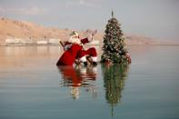 Issa Kassissieh, wearing a Santa Claus costume, gestures as he poses for a picture while sitting next to a Christmas tree on a salt formation in the Dead Sea, near Ein Bokeq