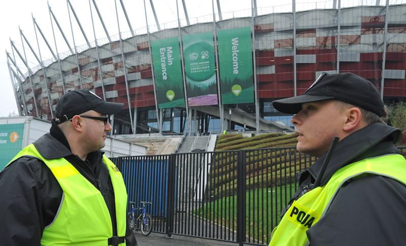 Police officers guard the National Stadium, the venue of the U.N. Climate Change Conference, in Warsaw, Poland, Sunday, Nov. 10, 2013. Climate envoys from rich countries, emerging economies and low-lying nations at risk of being swamped by rising seas will meet in Poland Monday for the next two weeks to lay the groundwork for a new global warming pact. (AP Photo/Alik Keplicz)