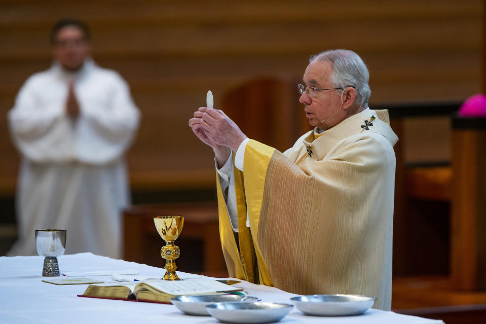 FILE - In this Sunday, June 7, 2020 file photo, Archbishop Jose H. Gomez holds a Communion wafer as he celebrates the the Solemnity of the Most Holy Trinity, a Mass with churchgoers present at the Cathedral of Our Lady of the Angels in downtown Los Angeles. Despite calls from some of its members for a delay, the U.S. Conference of Catholic Bishops plans to devote part of its national meeting in June 2021 to the sensitive issue of which Catholics are worthy of receiving Communion. (AP Photo/Damian Dovarganes, File)