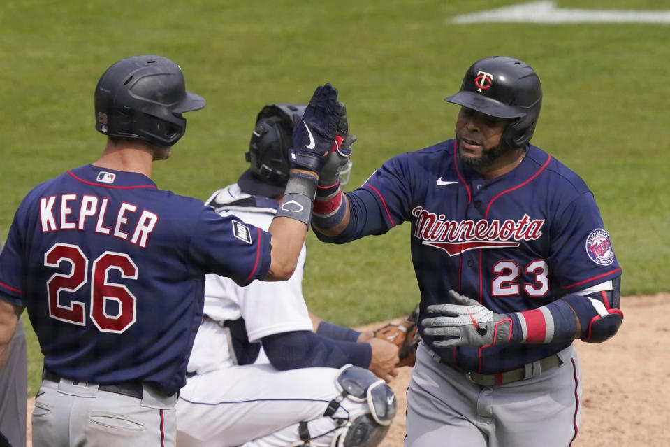 Minnesota Twins designated hitter Nelson Cruz (23) is greeted by Max Kepler after a solo home run during the seventh inning of a baseball game against the Detroit Tigers, Tuesday, April 6, 2021, in Detroit. (AP Photo/Carlos Osorio)