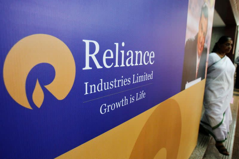 A woman walks past a poster of Reliance Industries installed outside the venue of the company's annual general meeting in Mumbai