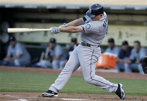 Seattle Mariners' Kyle Seager singles off of Oakland Athletics pitcher Tommy Milone to score Casper Wells during the first inning of a baseball game in Oakland, Calif., Friday, July 6, 2012. (AP Photo/Jeff Chiu)