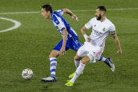 Real Madrid's Karim Benzema, right, fights for the ball with Alaves' Tomas Pina during the Spanish La Liga soccer match between Alaves and Real Madrid at Mendizorroza stadium in Vitoria, Spain, Saturday, Jan. 23, 2021. (AP Photo/Alvaro Barrientos)