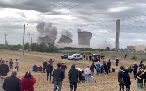People look on demolition of Didcot power station structure in Didcot - Credit: Mark Hodson/Reuters