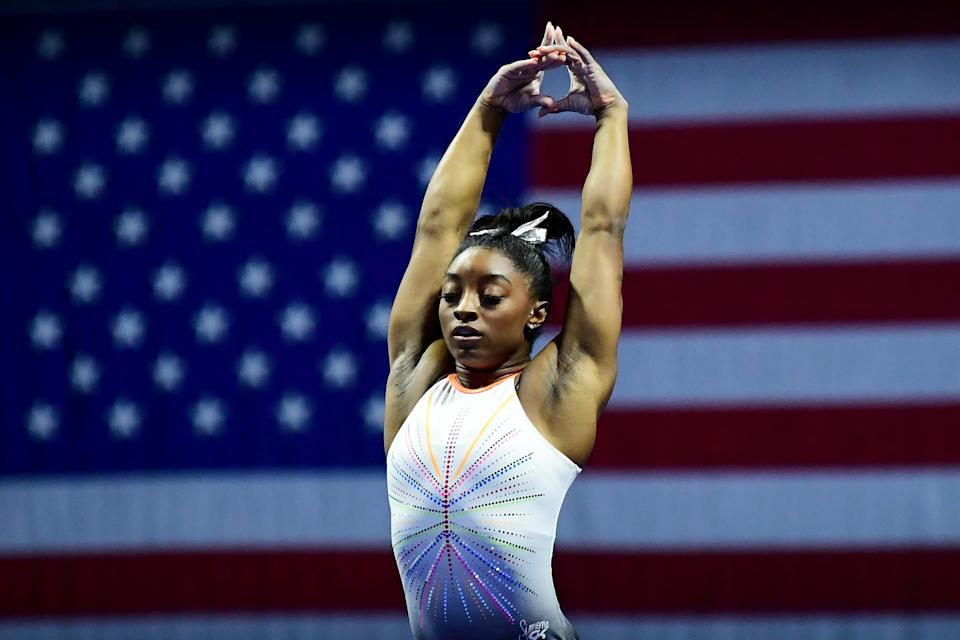Simone Biles poses in front of the American flag