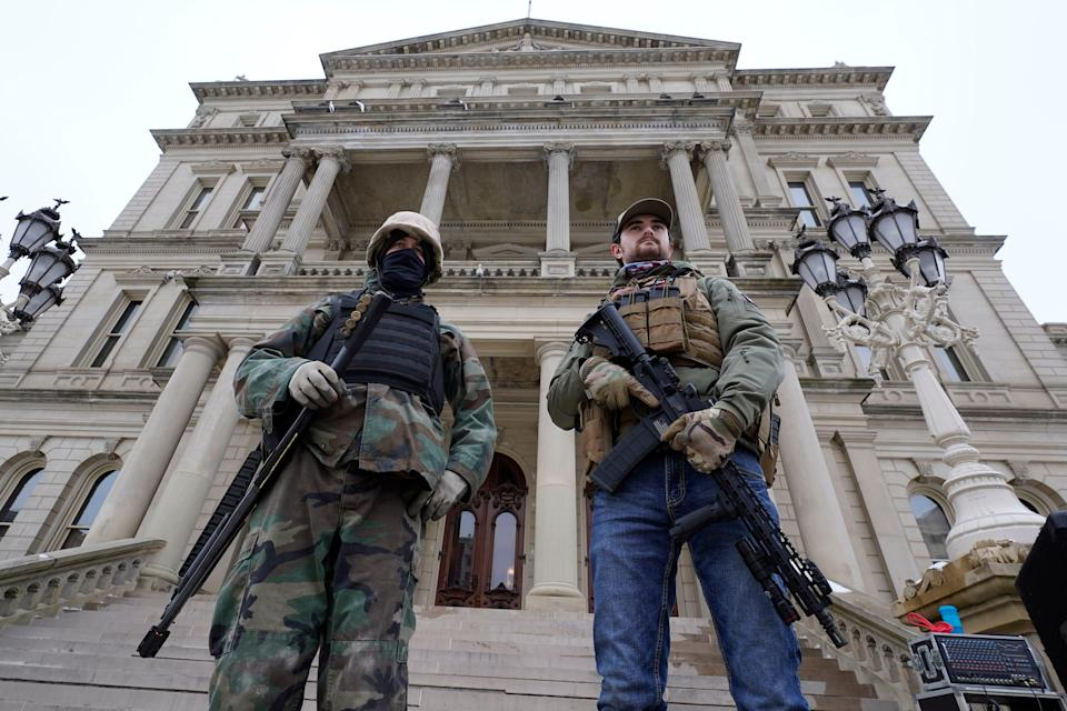 In this Jan. 6, 2021 file photo, armed men stand on the steps at the State Capitol after a rally in support of President Donald Trump in Lansing, Mich.