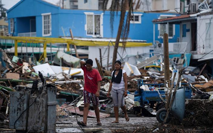 People walk near damaged houses and fallen electricity poles after the passage of Storm Iota, in Providencia - Nathalia Angarita/REUTERS