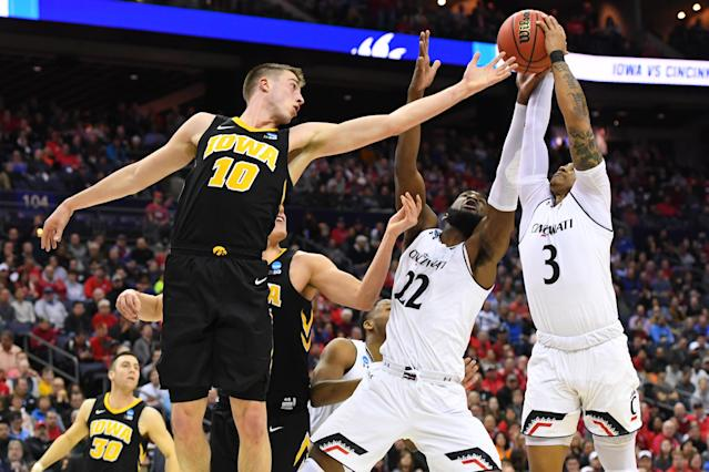 <p>Justin Jenifer #3 and Eliel Nsoseme #22 of the Cincinnati Bearcats fight for a rebound against Joe Wieskamp #10 of the Iowa Hawkeyes in the first round of the 2019 NCAA Men's Basketball Tournament held at Nationwide Arena on March 22, 2019 in Columbus, Ohio. (Photo by Jamie Schwaberow/NCAA Photos via Getty Images) </p>