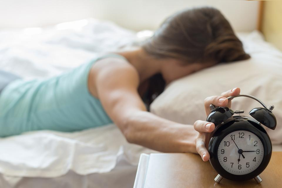A tired woman in bed hits her alarm clock to stop it from going off.