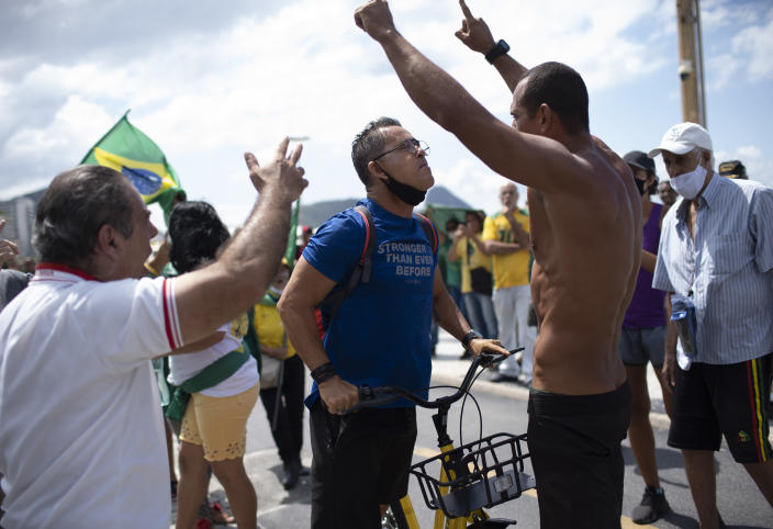 An opponent, center left, confronts supporters of Brazilian President Jair Bolsonaro during a demonstration supporting Bolsonaro after leaders of all three branches of the armed forces jointly resigned following the replacement of the defense minister, on Copacabana beach in Rio de Janeiro, Brazil, Wednesday, March 31, 2021. (AP Photo/Silvia Izquierdo)