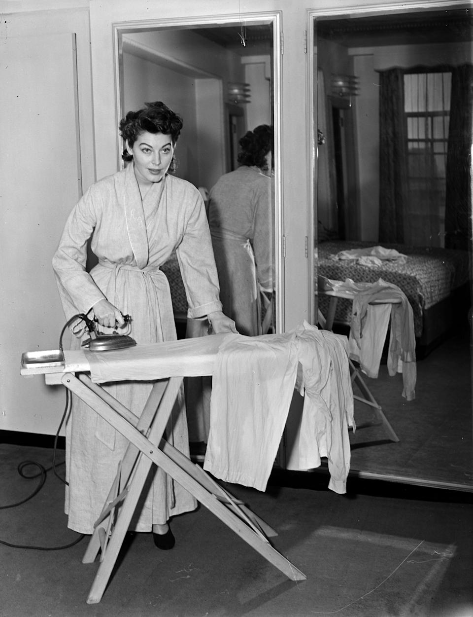 Gardner takes a break from the glitter to iron her pajamas in this 1950 photo.