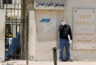 A man wearing protective face mask and gloves stands outside the Institute of Research for Tropical Medicine amid concerns about the spread of the coronavirus disease (COVID-19), in Cairo