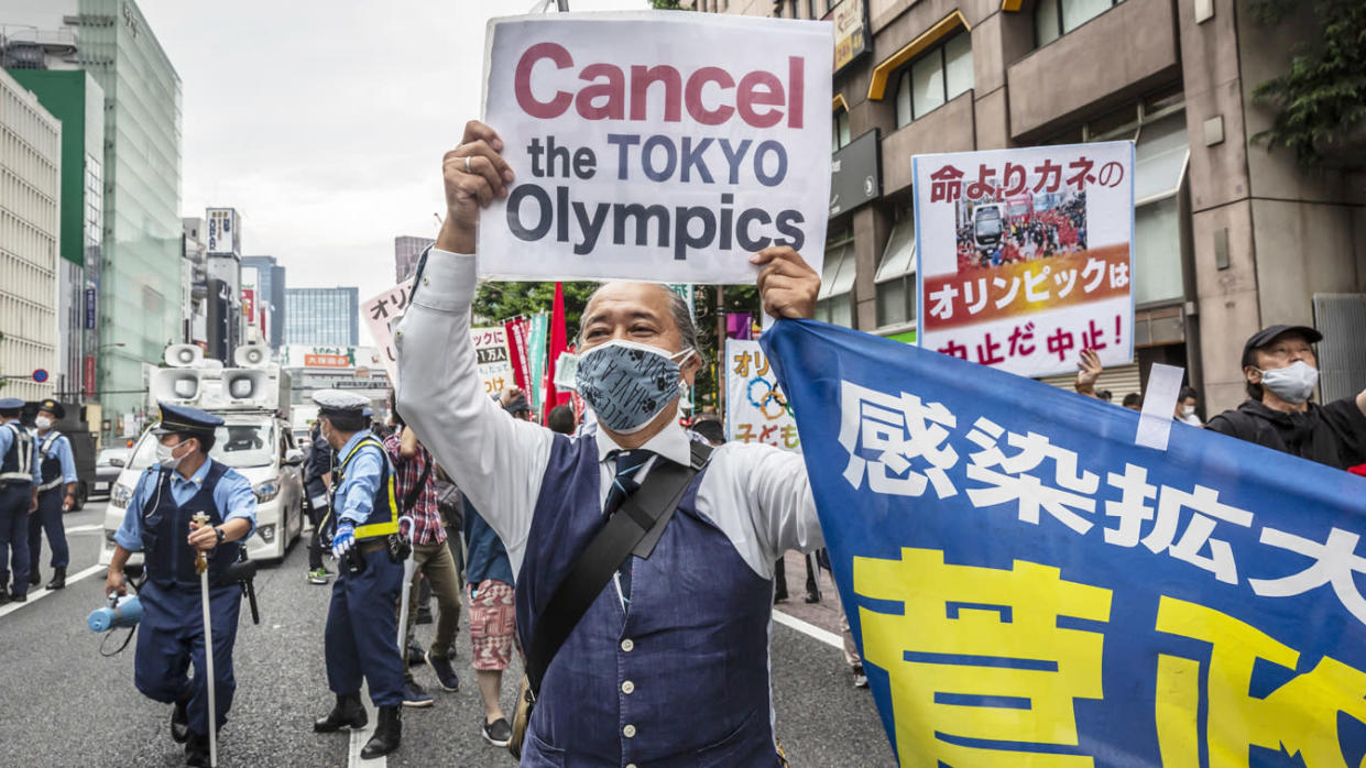 A protester holds a placard during a demonstration against the forthcoming Tokyo Olympic Games on June 06, 2021 in Tokyo, Japan. (Yuichi Yamazaki/Getty Images)