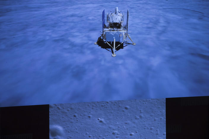 In this photo released by Xinhua News Agency, a screen shows the landed Chang'e-5 spacecraft and a moon surface picture, below, taken by camera aboard Chang'e-5 spacecraft during its landing process, at Beijing Aerospace Control Center (BACC) in Beijing on Tuesday, Dec. 1, 2020. A Chinese spacecraft landed on the moon Tuesday to bring back lunar rocks to Earth for the first time since the 1970s, the government announced. (Jin Liwang/Xinhua via AP)