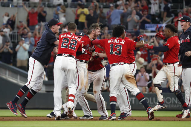 Atlanta Braves' Josh Donaldson, center, is mobbed by his teammates after driving in the winning run with a base hit in the ninth inning of a baseball game against the Washington Nationals, Friday, July 19, 2019, in Atlanta. (AP Photo/John Bazemore)